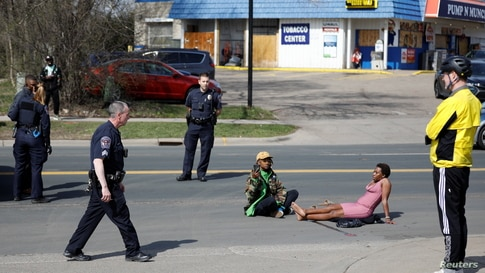 Phoenix Robles and Dorcas Monari block road traffic on Humboldt Avenue in front of the Brooklyn Center Police Department as protests continue days after former police officer Kim Potter fatally shot Daunte Wright, in Brooklyn Center, Minnesota, April 18, 2021.