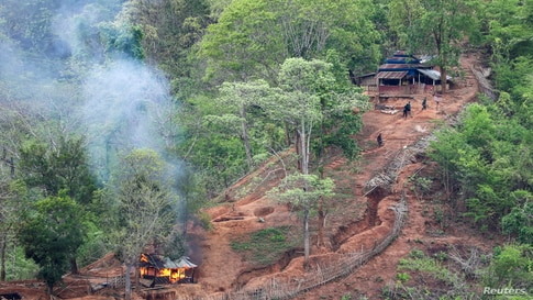 Ethnic minority Karen troops are seen after setting fire to a building inside a Myanmar army outpost near the Thai border, which is seen from the Thai side on the Thanlwin, also known as Salween riverbank in Mae Hong Son province, Thailand.
