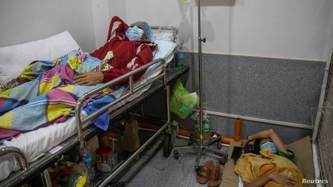A COVID-19 patient rests while his daughter and watcher sleeps on the floor of the COVID-19 emergency room at the government National Kidney and Transplant Institute in Quezon City, Metro Manila, Philippines.