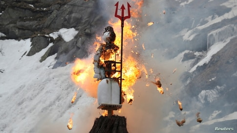 The Boeoegg, a snowman made of wadding and filled with firecrackers, is burning in a bonfire on the landmark of Devil's Bridge in the Schoellenen Gorge near the Alpine resort of Andermatt, Switzerland, April 19, 2021.