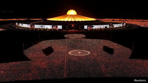Buddhist monks of the Dhammakaya temple attend a meditation ceremony on Earth Day and light 330,000 candles arranged in the shape of the earth to set a Guinness World Record, in Pathum Thani province, Thailand.