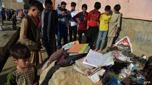 Onlookers stand next to the backpacks and books of victims following yesterday's multiple blasts outside a girls' school in…