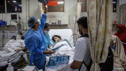Rohan Aggarwal, 26, a resident doctor treating patients suffering from the coronavirus disease (COVID-19), looks at a patient's x-ray scan, inside the emergency room of Holy Family Hospital, during his 27-hour shift in New Delhi, India, May 1, 2021.