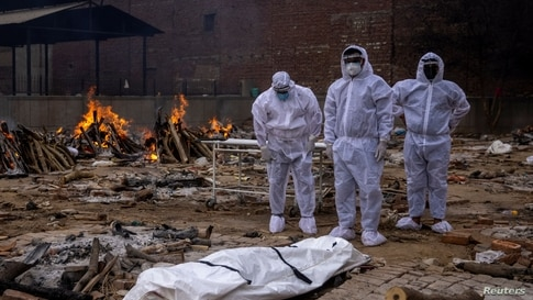 Men wearing protective suits stand next to the body of their relative, who died from the coronavirus disease (COVID-19).