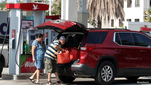 A man loads a 5 gallon gas tanks in his car after filling multiple of them up at a Wawa gas station, following a cyberattack…