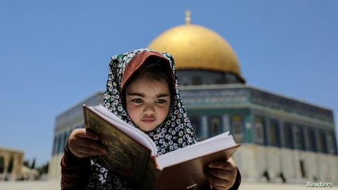 A girl sits with a holy book as the Dome of the Rock is seen in the background at the compound that houses al-Aqsa Mosque,…