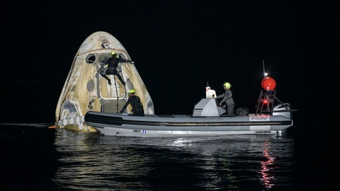 Support teams work around the SpaceX Crew Dragon Resilience spacecraft after shortly it landed with NASA astronauts and a Japanese astronaut aboard in the Gulf of Mexico off the coast of Panama City, Florida.
