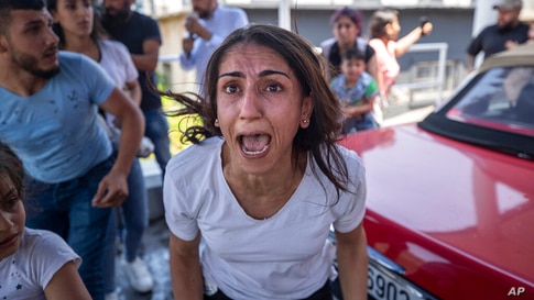 A Syrian woman screams for help for her husband who was injured by stone throwing by members of the Lebanese Forces group, who…