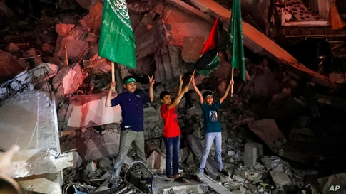 Palestinian children wave green Hamas and their national flags as they stand on the rubble of a destroyed building while…