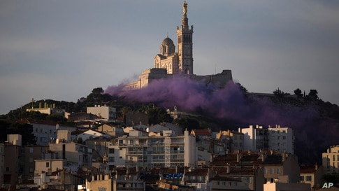 Culture workers set off smoke flares after sunrise in front of the Notre-Dame de la Garde basilica in Marseille, southern…