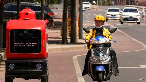 A delivery man passes by an autonomous delivery vehicle from JD.com on the streets of Beijing on Friday, May 28, 2021. China's…