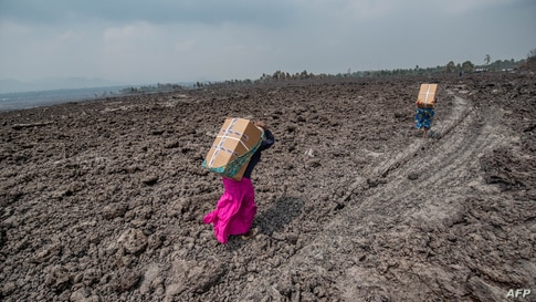 Residents carry goods on their backs while they cross a lava covered field in Buhene, north of Goma, Democratic Republic of Congo.
