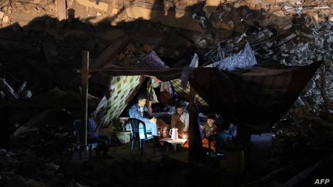 Palestinians sit in a tent that has been set up on top of the ruins of a building destroyed in recent Israeli airstrikes, in Gaza City, May 24, 2021.