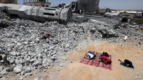 Palestinian Muslim worshippers pray near the rubble of a destroyed mosque in Beit Lahia, in the northern Gaza Strip.