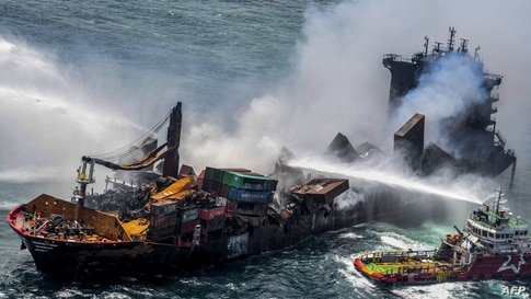 Smoke billow from the Singapore-registered container ship MV X-Press Pearl, as vessels douse off the fire in the sea off Sri Lanka's Colombo Harbor in Colombo.