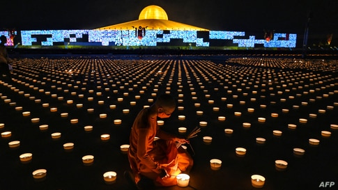 A Buddhist monk lights candles to commemorate Visakha Bucha Day, a celebration of the birth, enlightenment and death of the Lord Buddha, at Wat Dhammakaya Buddhist temple in Bangkok, Thailand.