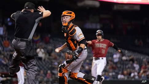 Umpire Nick Mahrley (L) calls a foul ball as San Francisco Giants catcher Buster Posey, middle, questions the call during the ninth inning of a baseball game in Phoenix, AZ, May 26, 2021.