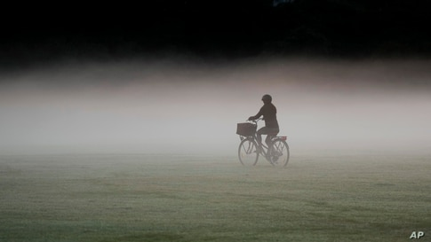 A woman rides her bicycle through a heavy mist in a park as the sun rises in Sydney, Australia.