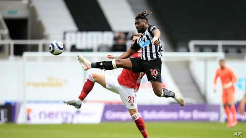 Newcastle's Allan Saint-Maximin, 10, competes for the ball with Arsenal's Calum Chambers during the English Premier League soccer match between Newcastle United and Arsenal at St James' Park stadium, in Newcastle, England.