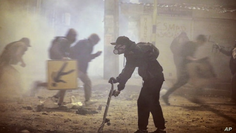 Anti-government protesters run during clashes with the police in Bogota, Colombia, May 26, 2021.