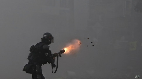 A police officer fires tear gas at protesters during a strike against tax reform in Cali, Colombia, May 3, 2021.