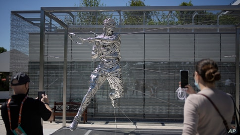 Spectators take photos of a new statue of Spain's Rafael Nadal on day two of the French Open tennis tournament at Roland Garros in Paris, France.