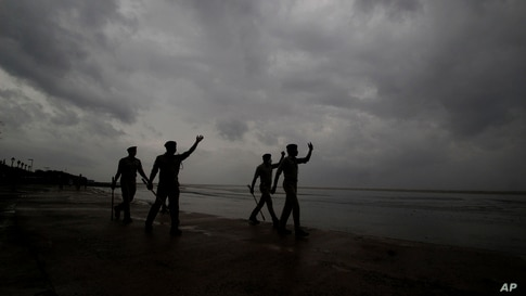 Policemen ask people to move to cyclone shelters as they patrol a beach in Balasore district in Odisha, India.