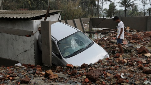 A man looks at a car damaged by Cyclone Yaas that made a landfall at Digha on the Bay of Bengal coast, West Bengal state, India.