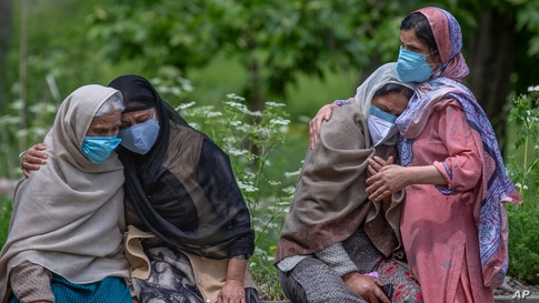 Women comfort family members of a person who died of COVID-19 at a crematorium in Srinagar, Indian-controlled Kashmir.