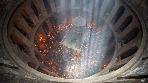 Christian pilgrims hold candles as they gather during the ceremony of the Holy Fire at Church of the Holy Sepulchre, where many Christians believe Jesus was crucified, buried and rose from the dead, in the Old City of Jerusalem, May 1, 2021.