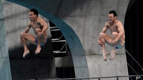 Mexico's Yahel Castillo Huerta and Juan Manuel Celaya Hernandez perform a dive in the men's synchronized 3-meter springboard final at the FINA Diving World Cup at the Tokyo Aquatics Centre in Tokyo, Japan.