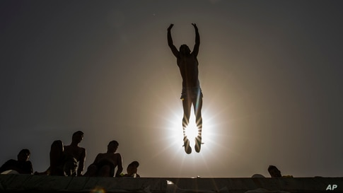 A youth jumps into the Mediterranean Sea off the corniche during a lockdown to curb the spread of coronavirus in Saida, Lebanon, May 2, 2021.
