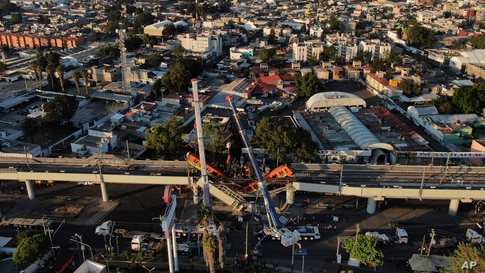 An aerial view of subway cars dangle at an angle from a collapsed elevated section of the metro, in Mexico City, killing at least 23 people and injuring at least 79.