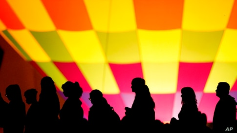 People are silhouetted against a hot air balloon during a balloon glow as part of Memorial Day weekend activities on the grounds of the National World War I Museum and Memorial, Sunday, May 30, 2021, in Kansas City, Mo. (AP Photo/Charlie Riedel)