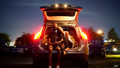 """Kene Daniels, right, and Amman Raheem watch a documentary called """"Rebuilding Black Wall Street,"""" during a drive-in screening of documentaries during centennial commemorations of the Tulsa Race Massacre, May 26, 2021, in Tulsa, Oklahoma."""