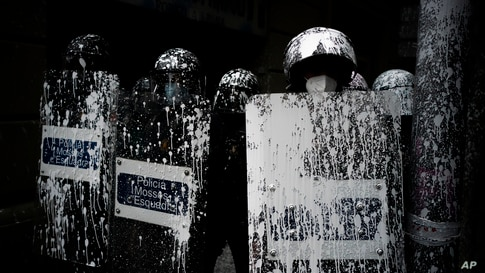 Riot police officers covered by paint thrown by protesters stand guard as activists try to stop the eviction of Axel Altadill, 28 from his apartment in Barcelona, Spain.