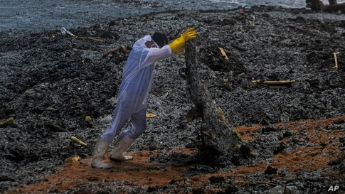 A Sri Lankan navy soldier hauls debris washed ashore from the burning Singaporean ship MV X-Press Pearl which is anchored off Colombo port at Kapungoda, out skirts of Colombo.