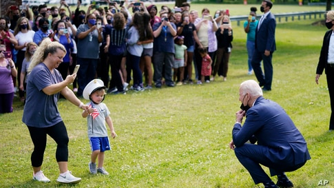 President Joe Biden stops outside at York High School to greet a child and his mother in Yorktown, Virginia.