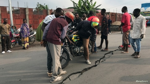 People look at a crack on the road caused by earth tremors as aftershocks following the eruption of Mount Nyiragongo volcano near Goma, in the Democratic Republic of Congo.