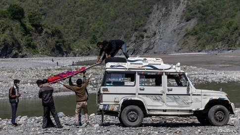 Relatives of Pramila Devi, 36, who died from complications related to the COVID-19, unload her body from a jeep before her cremation, on the banks of the river Ganges in Pauri Garhwal, in the northern state of Uttarakhand, India.