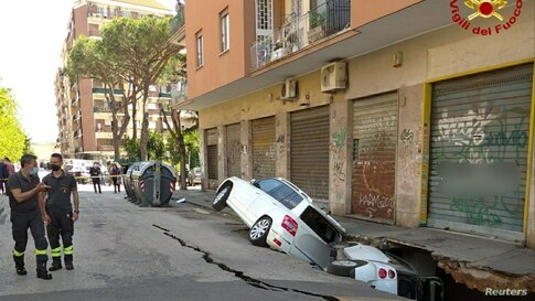 Cars are seen stuck sideways in a huge hole that has opened up next to an apartment building in Rome, Italy.