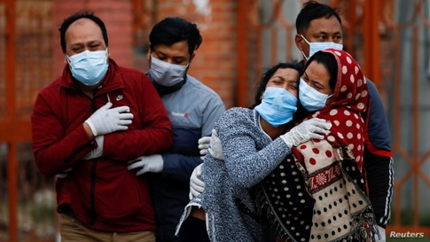 Family members mourn a COVID-19 victim as the country recorded the highest daily increase in death since the pandemic began, in Kathmandu, Nepal.