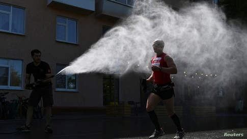 A participant of a half-marathon race is sprayed with water during hot weather in Omsk, Russia, May 30, 2021.