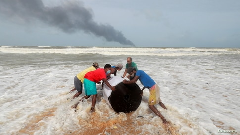 Smoke rises from a fire onboard the MV X-Press Pearl container ship in the seas off the Colombo Harbor as villagers push the cargo spilled from it on a beach in Ja-Ela, Sri Lanka.