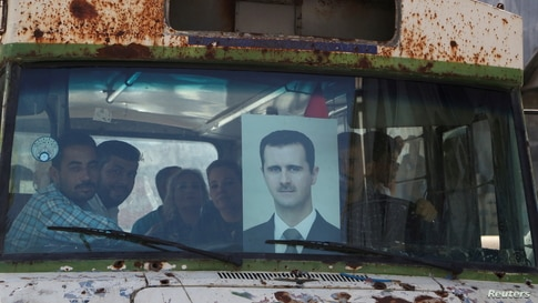 People ride on a bus as they head to a polling station to cast their vote, during the presidential elections, in Damascus, Syria.
