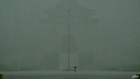 A man walks in heavy rain caused by Tropical Storm Choi-Wan in front of the Chiang Kai-shek Memorial Hall in Taipei on June 4,…