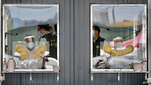 Medical personnel are seen behind their sealed work areas at a swab test screening area for the Covid-19 coronavirus in New…