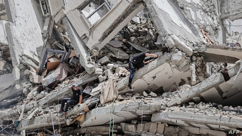 Palestinian workers clear the rubble and debris in Gaza City's al-Rimal neighbourhood, which was targeted by Israeli strikes…