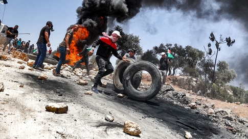 Palestinian protesters set tires aflame during clashes with Israeli security forces following a demonstration in the village of…