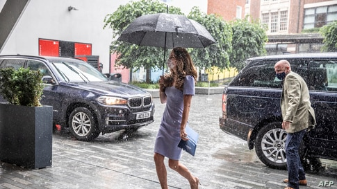 Britain's Catherine, Duchess of Cambridge, shelters from the rain under an umbrella as she arrives at the London School of…